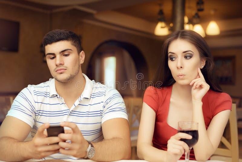 Noivo espiando da menina curiosa em Smartphone fotos de stock royalty free