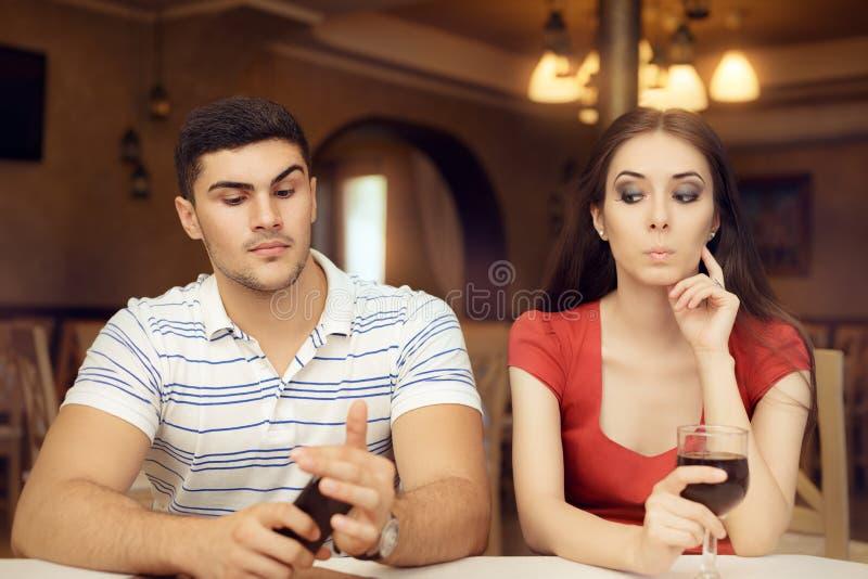 Noivo espiando da menina curiosa em Smartphone foto de stock