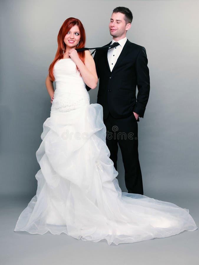 Noivo feliz da noiva do casal no fundo cinzento imagens de stock royalty free