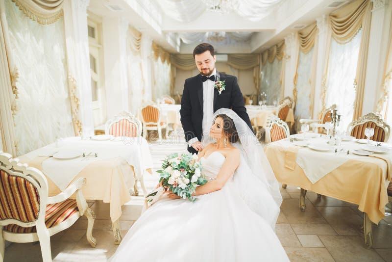 Noivo lindo que abraça delicadamente a noiva à moda Momento sensual de pares luxuosos do casamento fotografia de stock royalty free