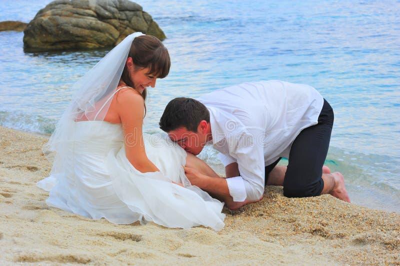 Noivo Loving que beija com paixão o pé da sua noiva imagem de stock royalty free