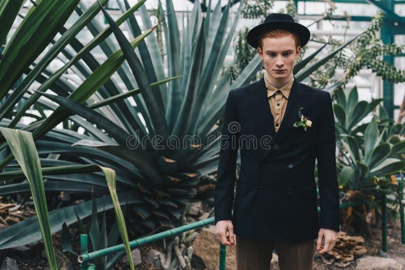 noivo novo à moda considerável no chapéu que está e que olha para baixo fotografia de stock royalty free
