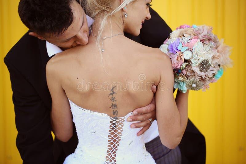 Noivo que beija sua noiva em ombros foto de stock royalty free