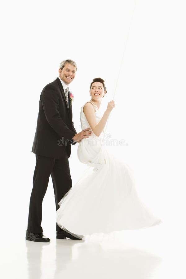 Noivo que empurra a noiva no balanço. fotografia de stock