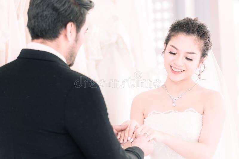 Noivo que guarda as mãos da noiva na cerimônia dos ternos do casamento foto de stock