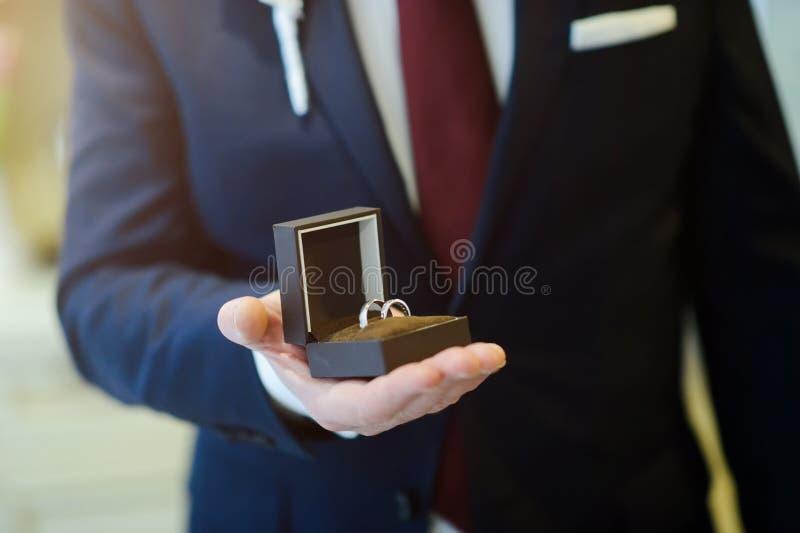 Noivo que guarda a caixa com alian?a de casamento fotografia de stock royalty free