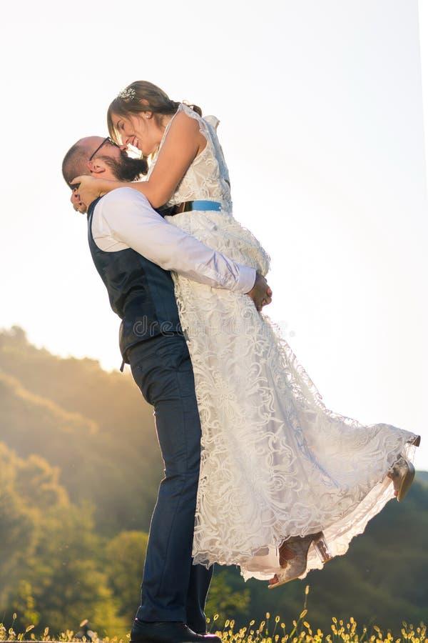 Noivo que guarda a noiva em seus braços imagens de stock royalty free