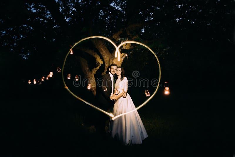 Noivos bonitos no parque da noite que guarda-se sob a árvore decorada com muitas lanternas Coração de Lightpainted imagem de stock royalty free