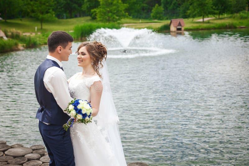 Noivos bonitos que sorriem na natureza perto do lago com fonte foto de stock
