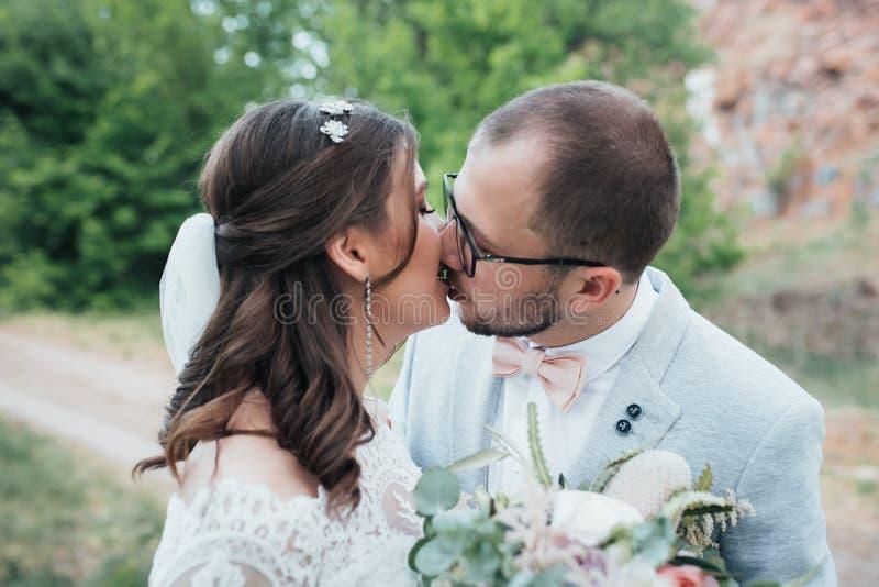 Noivos do beijo da fotografia do casamento em lugar diferentes imagem de stock