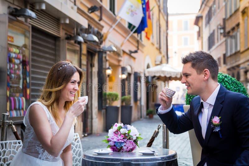 Noivos em um café bebendo da tabela em Roma, Itália fotografia de stock