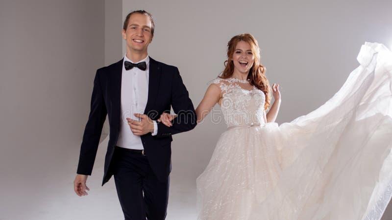 Noivos engraçados e felizes, dança e salto com a felicidade, casada Retrato do estúdio, fundo claro foto de stock