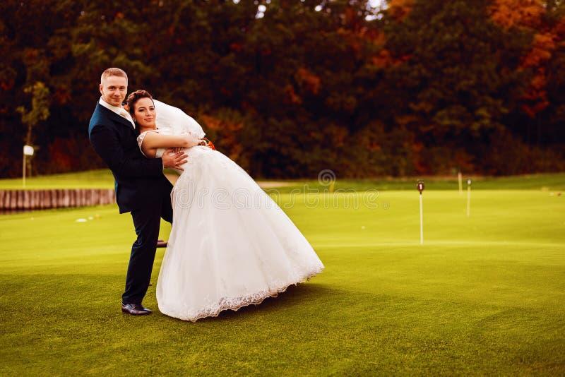 Noivos engraçados no campo do golfe fotografia de stock royalty free