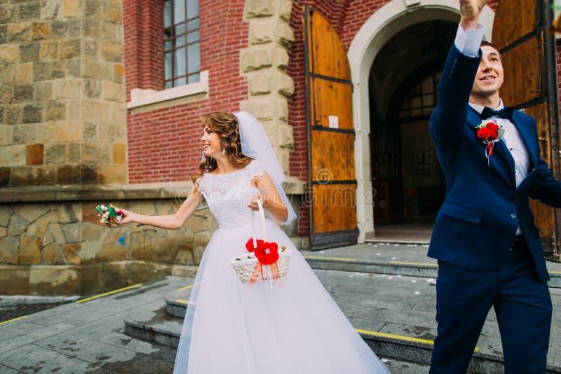 Noivos felizes que saem da igreja após uma cerimônia de casamento tradicional fotografia de stock