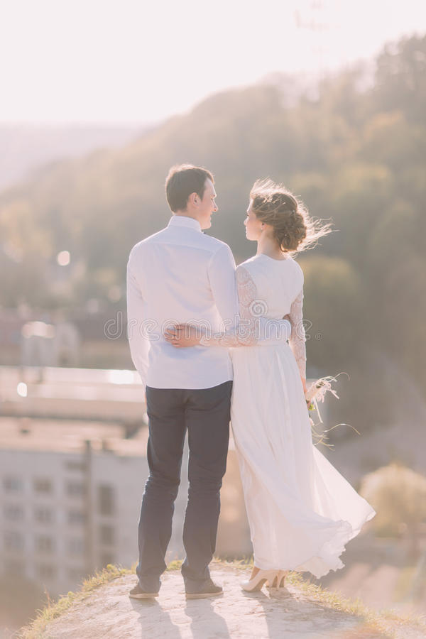 Noivos felizes românticos luxuosos que estão para trás no fundo da cidade ensolarada velha foto de stock royalty free
