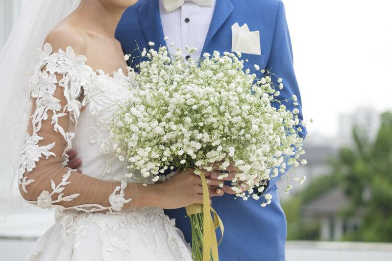 Noivos Holding Together no terno formal com ramalhete do casamento foto de stock
