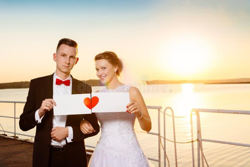 Noivos no cais no por do sol fotografia de stock royalty free