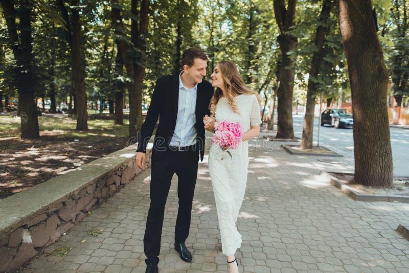 Noivos no dia do casamento que andam fora na natureza da mola Pares nupciais, homem feliz da mulher do recém-casado que abraça i imagem de stock royalty free