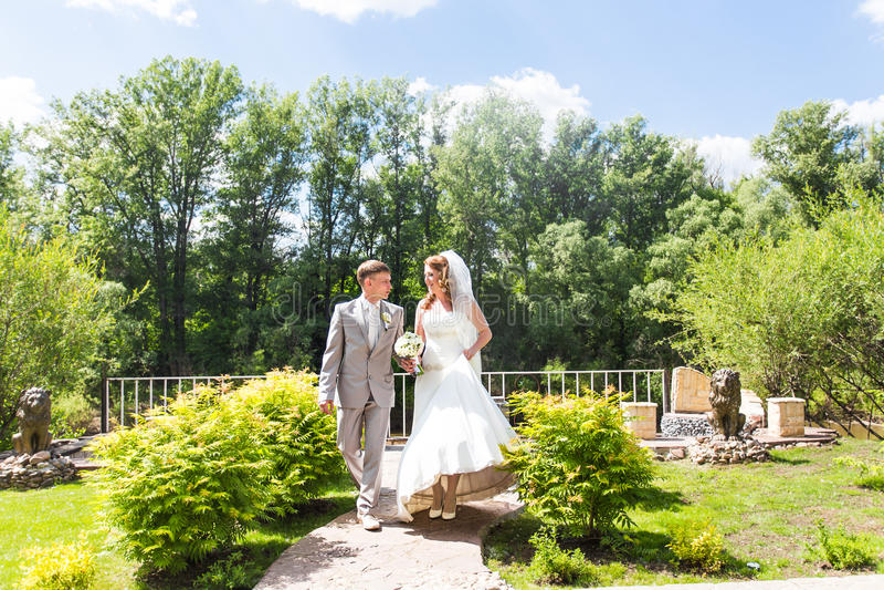 Noivos no dia do casamento que andam fora na natureza da mola Pares nupciais, mulher feliz do recém-casado e abraço do homem imagens de stock