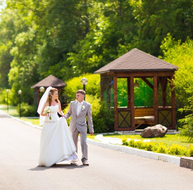 Noivos no dia do casamento que andam fora na natureza da mola Pares nupciais, mulher feliz do recém-casado e abraço do homem fotografia de stock royalty free