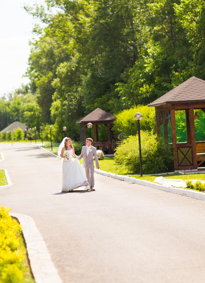 Noivos no dia do casamento que andam fora na natureza da mola Pares nupciais, mulher feliz do recém-casado e abraço do homem fotos de stock royalty free
