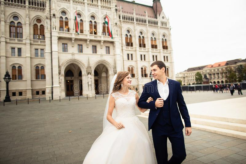 Noivos que abra?am na rua velha da cidade O par do casamento anda em Budapest perto da casa do parlamento fotografia de stock