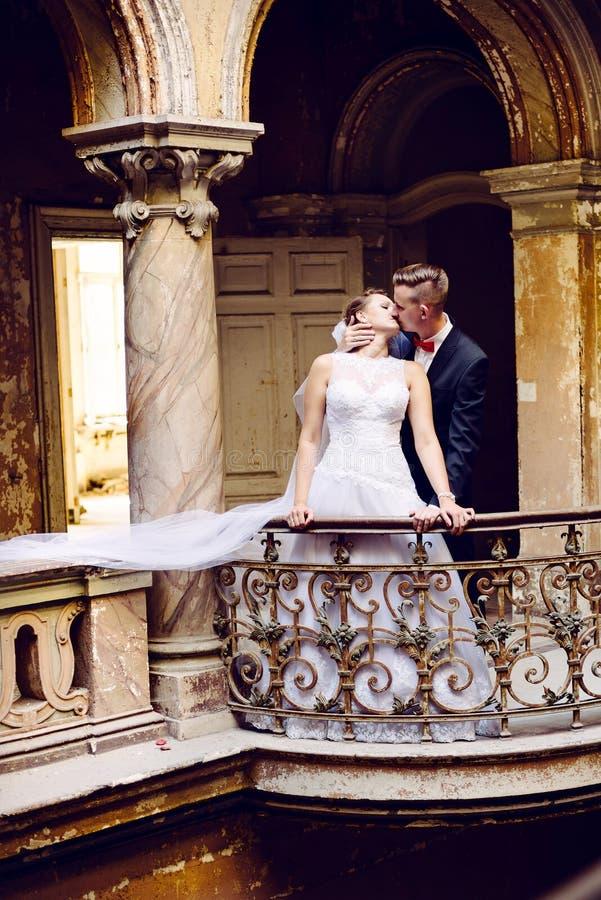 Noivos que beijam no balcão fotografia de stock