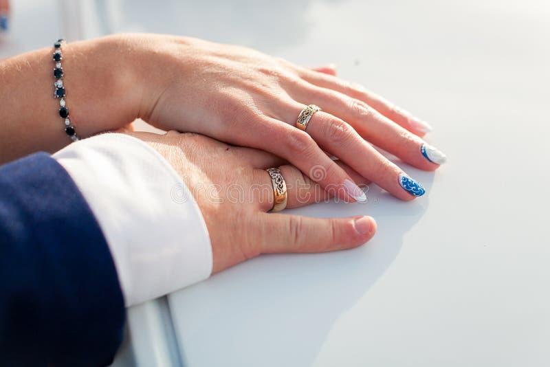 Noivos que guardam as mãos com alianças de casamento nele imagem de stock royalty free