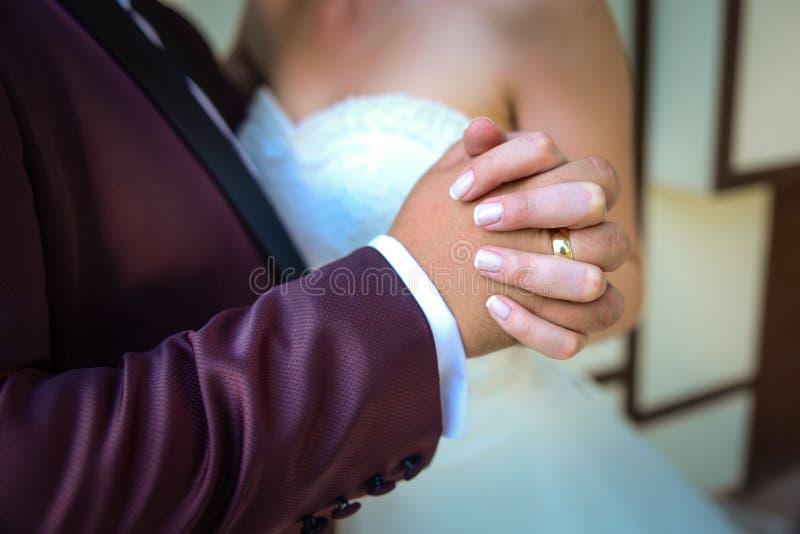 Noivos que guardam as mãos com aneis de noivado em seus dedos próximos acima do conceito do tiro do casamento da vista fotografia de stock