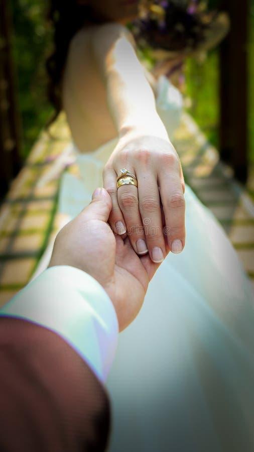 Noivos que guardam as mãos com aneis de noivado em seus dedos próximos acima do conceito do tiro do casamento da vista fotos de stock royalty free