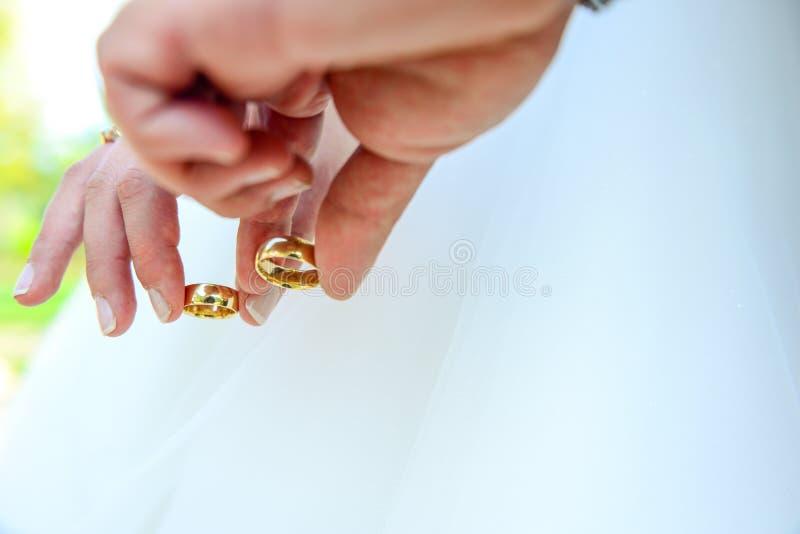 Noivos que guardam as mãos com aneis de noivado em seus dedos próximos acima do conceito do tiro do casamento da vista foto de stock royalty free