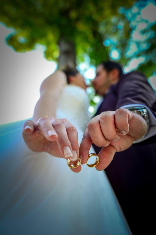 Noivos que guardam as mãos com aneis de noivado em seus dedos próximos acima do conceito do tiro do casamento da vista imagens de stock royalty free