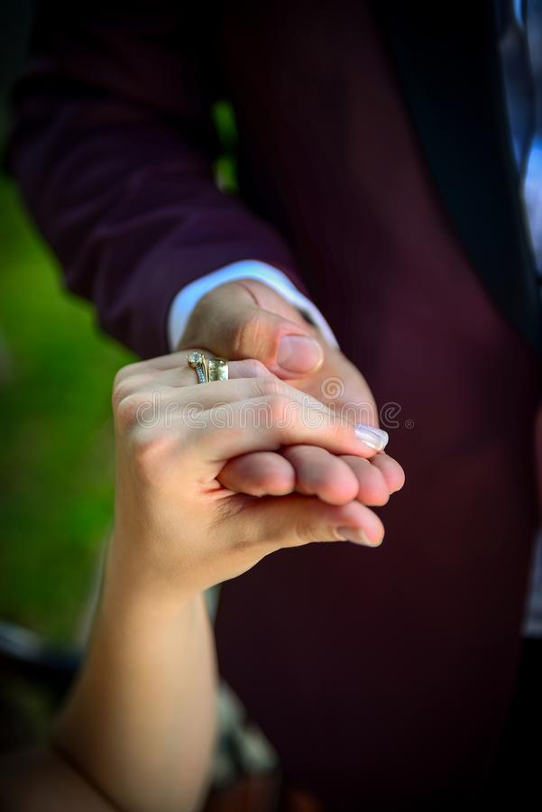 Noivos que guardam as mãos com aneis de noivado em seus dedos próximos acima do conceito do tiro do casamento da vista imagens de stock