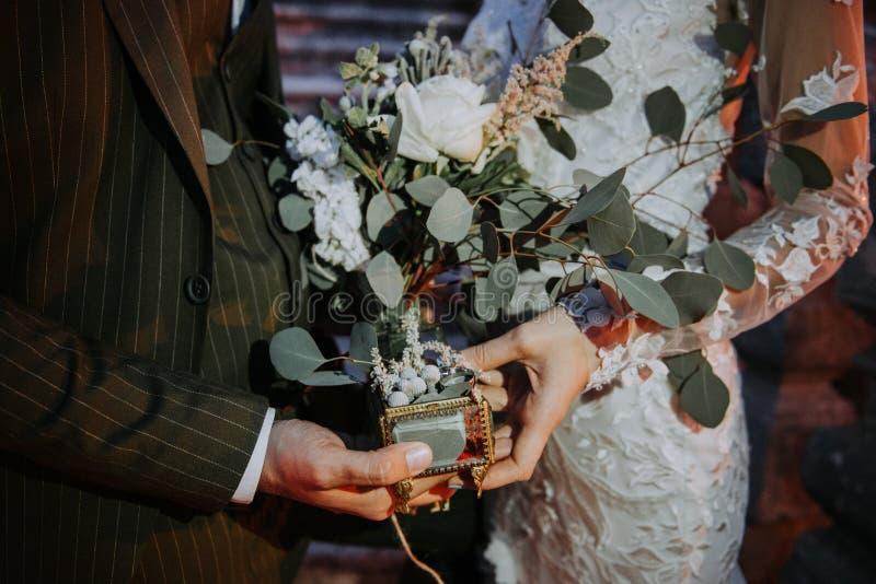 Noivos que guardam as mãos, e aliança de casamento bonita em sua mão Pares românticos que guardam-se mão do ` s em fotos de stock