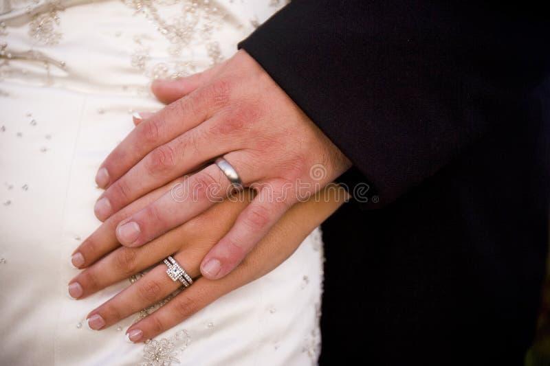 Noivos que guardam as mãos que mostram suas alianças de casamento imagens de stock