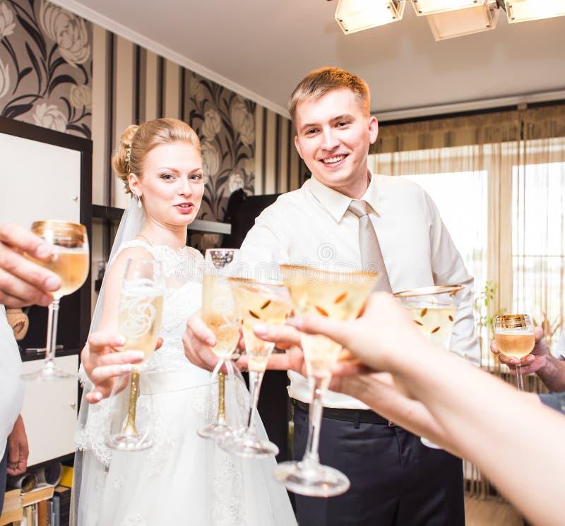 Noivos que guardam vidros do champanhe do casamento foto de stock royalty free
