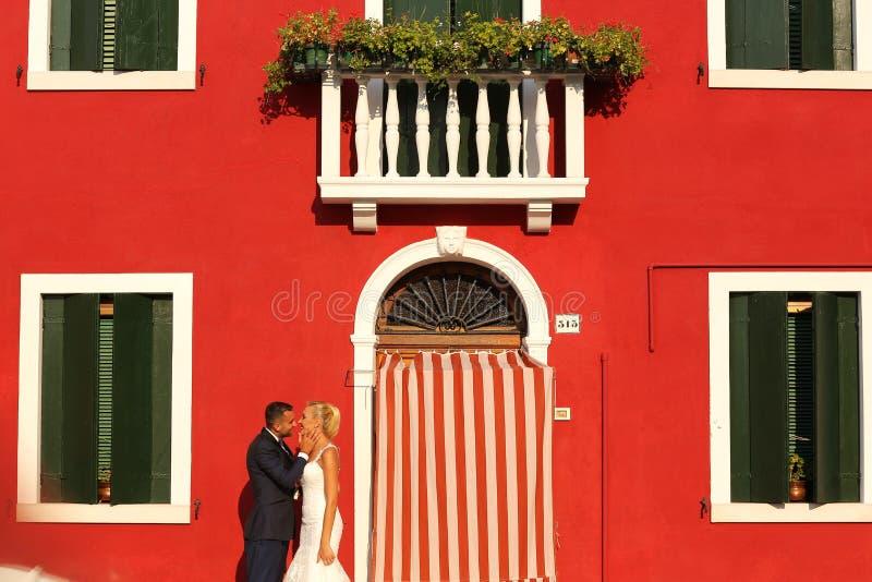 Noivos que levantam na frente de uma casa vermelha fotografia de stock royalty free
