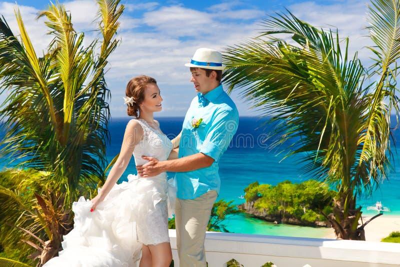 Noivos que têm o divertimento em uma praia tropical sob a palma t fotos de stock royalty free