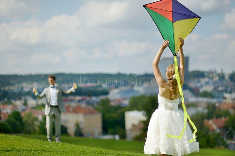 Noivos que voam um papagaio em um dia do casamento foto de stock royalty free