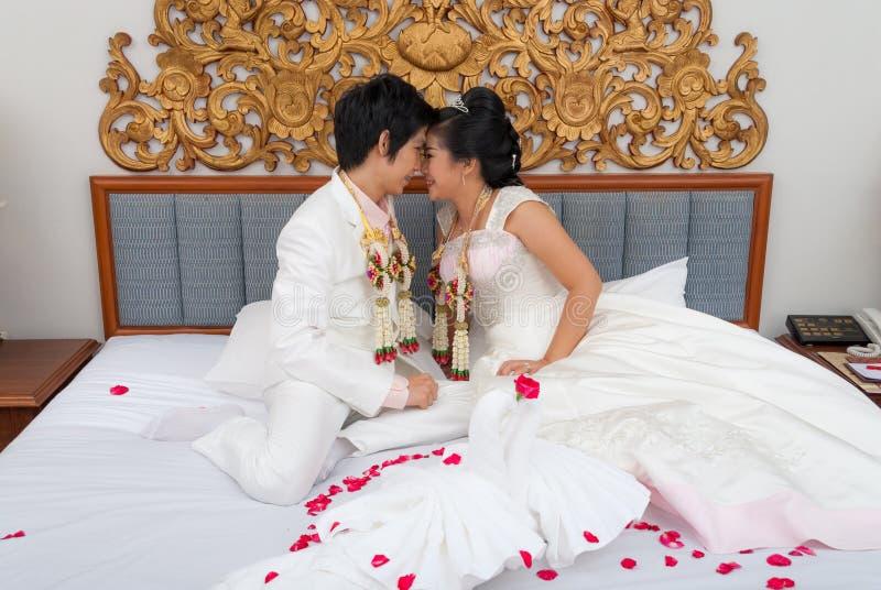 Noivos tailandeses asiáticos em uma cama no dia do casamento fotografia de stock royalty free