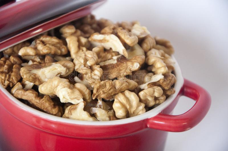 Noix épluchées dans une petite casserole rouge avec un casse-noix photographie stock