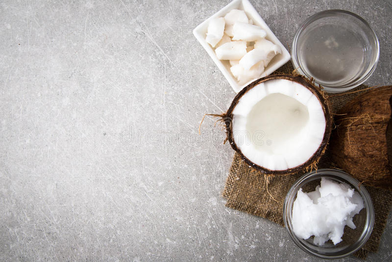 Noix de coco avec de l'huile de noix de coco dans le pot sur le fond en bois image stock