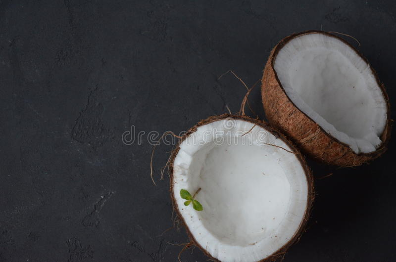 Noix de coco avec des fleurs de menthe et d'orhid, sur le fond foncé Copiez l'espace photo stock