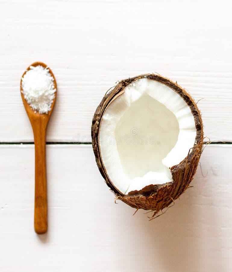 Noix de coco et cuillère sur un contexte en bois blanc photographie stock libre de droits