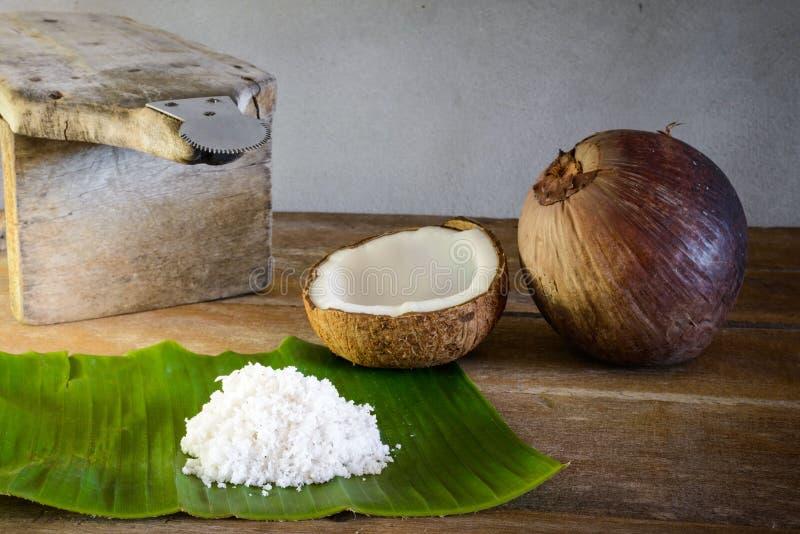 Noix de coco et flocons de noix de coco sur la feuille de banane et la râpe de noix de coco images libres de droits