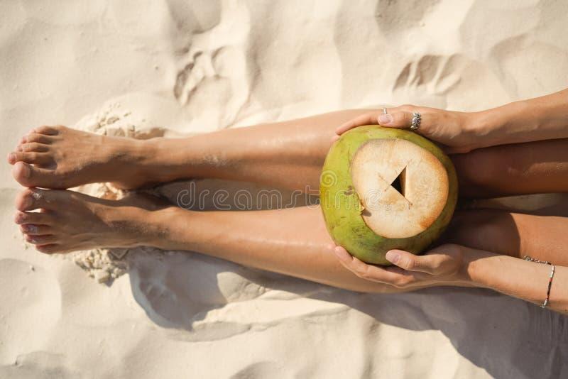 Noix de coco de participation de femme se reposant sur la plage tropicale photos libres de droits
