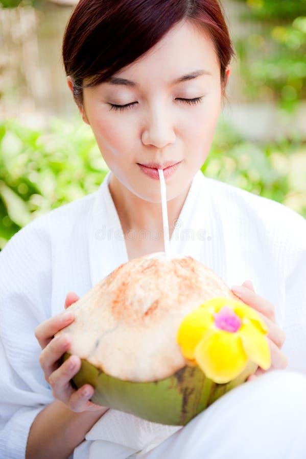 Noix de coco potable de femme photo libre de droits