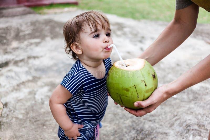 Noix de coco potable mignonne de petite fille photographie stock