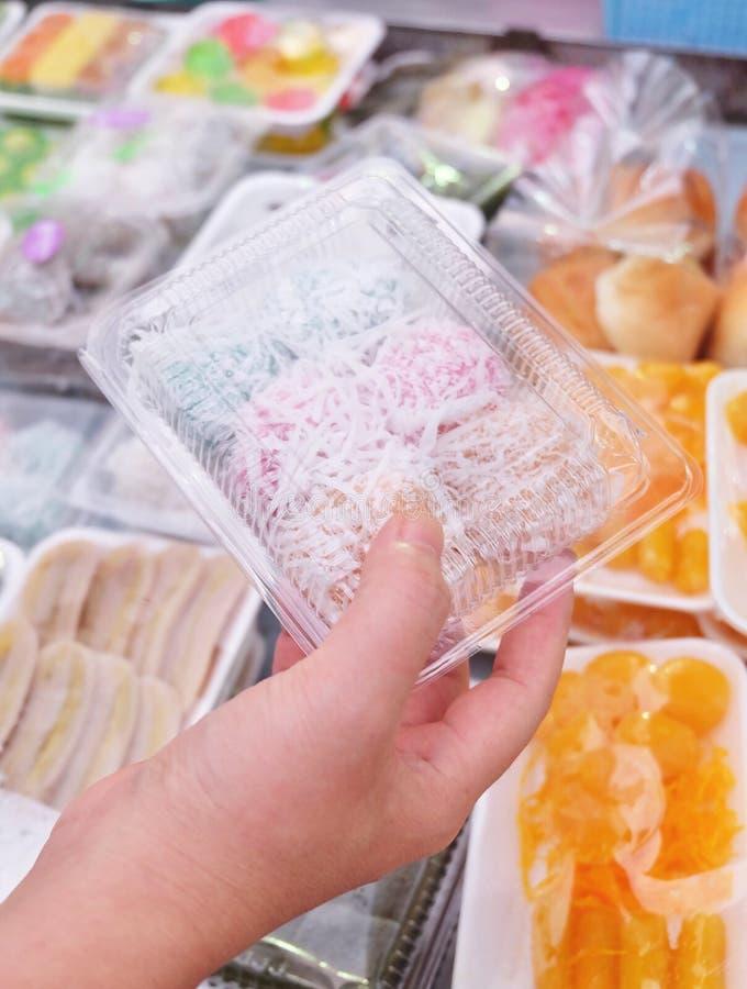 Noix de coco thaïlandaise Muchkins de participation de main dans la boîte en plastique image libre de droits
