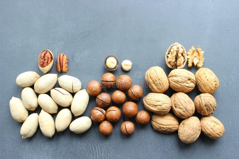 Noix, noisetiers d'Australie assortis et noix de pécan en gros plan sur la table en bois image stock